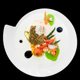 Salmon steak with vegetables in plate isolated on black Stock Photography