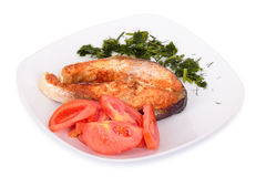 Salmon steak with vegetables on plate. Royalty Free Stock Images