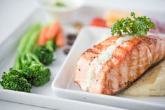 Salmon Steak with Vegetables. On white plate Royalty Free Stock Images