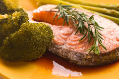 Salmon steak with vegetables on yellow plate Stock Photos
