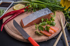 Salmon steak, view from the rind, butter, pepper, lemon and greens on a plate in restaurant. close-up. Top. Salmon steak, view from the rind, butter, pepper royalty free stock photo