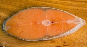 Salmon steak on wooden board Royalty Free Stock Photo