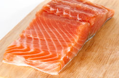 Salmon steak on wooden plank Stock Photography