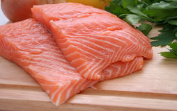 Salmon Steaks. Two fresh salmon steaks on a wooden cutting board royalty free stock photo