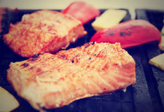 Salmon steaks being fried on grill, toned Royalty Free Stock Photography