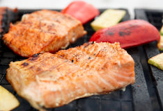 Salmon steaks being fried on grill Stock Photos