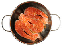 Salmon steaks being marinated in pot, isolated Royalty Free Stock Images