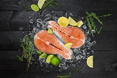 Salmon steaks on black wooden background. Top view Royalty Free Stock Photo