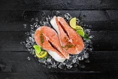 Salmon steaks on black wooden table background. Salmon steaks on ice on black wooden table top view. Fish food concept. Copy space Royalty Free Stock Photo