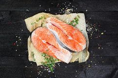 Salmon steaks on black wooden table. Top view Royalty Free Stock Photography