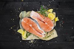 Salmon steaks on black wooden background top view. Salmon steaks on black wooden table top view Royalty Free Stock Photos