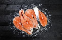 Salmon steaks on black wooden table top view. Salmon steaks on ice on black wooden table top view Royalty Free Stock Photography