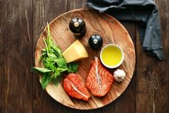 Salmon steaks with cheese and fresh ingredients. Raw humpback salmon steaks, cheese, rustic wooden background, above view. Fillet with fresh ingredients for Royalty Free Stock Photography