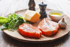 Salmon steaks with cheese and fresh ingredients. Raw humpback salmon steaks, cheese, rustic wooden background, above view. Fillet with fresh ingredients for Stock Image