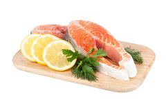 Salmon steaks on cutting board with lemons and herbs Stock Photography