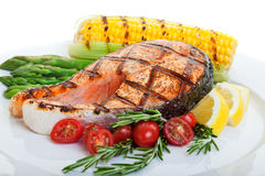 Salmon steaks. Grilled salmon steak with vegetables corn and asparagus Royalty Free Stock Photo