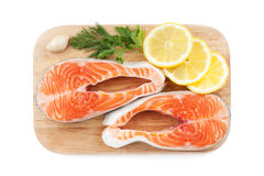 Salmon steaks with herbs and lemon slices on cutting board. Isolated on white background Royalty Free Stock Images