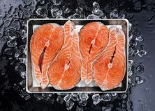 Salmon steaks on ice on black background. Copy space Stock Image