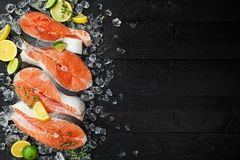 Salmon steaks on ice on black wooden table top view. Fish food concept. Copy space. Salmon steaks on ice on black wooden table top view. Copy space Stock Photo