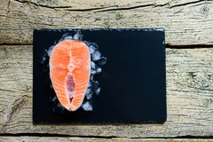 Salmon steaks on ice on black wooden table top view. Fish food concept. Copy space.  Stock Photo