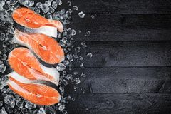 Salmon steaks on ice on black wooden table top view. Fish food concept. Copy space. Salmon steaks on ice on black wooden table top view. Copy space Royalty Free Stock Images