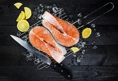 Salmon steaks on ice on black wooden table top view. Fish food concept. Copy space Royalty Free Stock Image