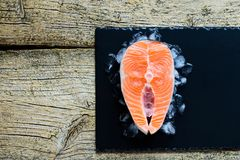 Salmon steaks on ice on black wooden table top view. Fish food concept. Copy space.  Royalty Free Stock Photos