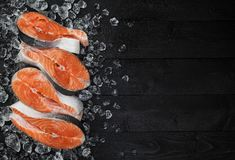 Salmon steak on ice on black wooden table top view, Fish food concept. Copy space. Salmon steaks on ice on black wooden table top view Royalty Free Stock Photos