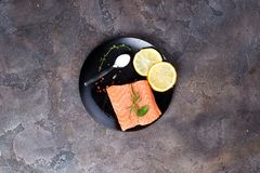 Salmon steaks on ice with lemon and salt on black plate. Lean proteins. Salmon steaks on ice with lemon and salt on black plate on a stone dark background. Fish Royalty Free Stock Photos
