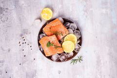 Salmon steaks on ice with lemon slice on wooden plate. Lean proteins. Salmon steaks on ice with lemon slice on wooden plate on a stone background. Fish food Royalty Free Stock Photo
