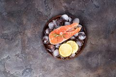 Salmon steaks on ice with lemon slice on wooden plate. Lean proteins. Salmon steaks on ice with lemon slice on wooden plate on a stone dark background. Fish Royalty Free Stock Photography