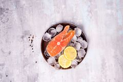 Salmon steaks on ice with lemon slice on wooden plate. On a stone background. Fish food concept. Top view with copy space Royalty Free Stock Photography