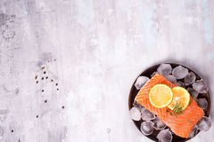 Salmon steaks on ice with lemon slice on wooden plate. On a stone background. Fish food concept. Top view with copy space Royalty Free Stock Photo