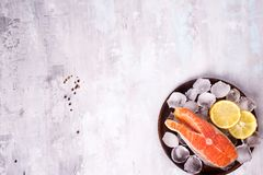 Salmon steaks on ice with lemon slice on wooden plate. On a stone background. Fish food concept. Top view with copy space Stock Photo