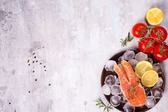 Salmon steaks on ice with lemon slice on wooden plate with tomato. Salmon steaks on ice with lemon slice and tomato on wooden plate on a stone light background Stock Photography