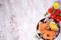Salmon steaks on ice with lemon slice on wooden plate with tomato. Salmon steaks on ice with lemon slice and tomato on wooden plate on a stone light background Stock Photos