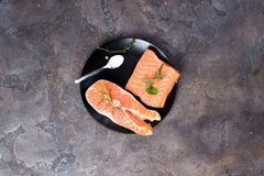 Salmon steaks on ice with salt on black plate. Lean proteins. Salmon steaks on ice with salt on black plate on a stone dark background. Fish food concept. Top Stock Images