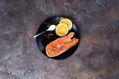 Salmon steaks on ice withlemon slice on wooden plate. Salmon steaks on ice with lemon and salt on wooden plate on a stone dark background. Fish food concept. Top Royalty Free Stock Photo