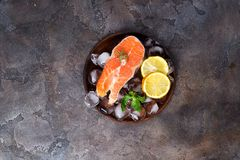 Salmon steaks on ice withlemon slice on wooden plate. On a stone dark background. Fish food concept. Top view with copy space Royalty Free Stock Photography
