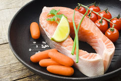Salmon steaks in the iron pan  with vegetables Royalty Free Stock Photos