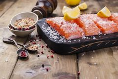 Salmon steaks with large salt, lemon and spices. Preparation of tasty and healthy food. Wooden background and Place for text. Seafood. Healthy food Stock Photos