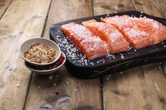 Salmon steaks with large salt and spices. Preparation of tasty and healthy food. Wooden background and Place for text. Seafood. Healthy food Royalty Free Stock Photos