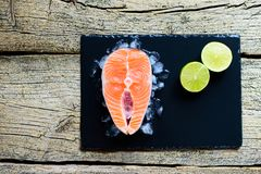 Salmon steaks with lime on ice on black wooden table top view. Fish food concept. Copy space.  Royalty Free Stock Photos