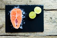 Salmon steaks with lime on ice on black wooden table top view. Fish food concept. Copy space.  Royalty Free Stock Images
