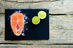 Salmon steaks with lime on ice on black wooden table top view. Fish food concept. Copy space.  Stock Photos