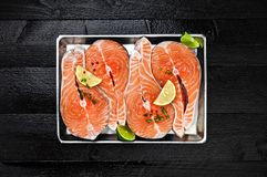 Salmon steaks on metal tray on black wooden table top view. Fish food concept. Copy space Royalty Free Stock Photos