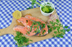 Salmon steaks prepared for baking. Spiced with salt, lemon, parsley, oil, garlic... Royalty Free Stock Photos