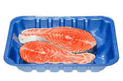 Salmon Steaks in a Tray. Two salmon steaks packaged in a blue tray. Isolated on white Royalty Free Stock Photography