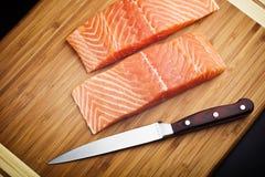 Salmon steaks on wooden board. Salmon steaks on grainy wooden board along side  sharp stainless steel kitchen knife Stock Image