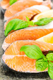 Salmon on stone with basil and lemon Stock Photography